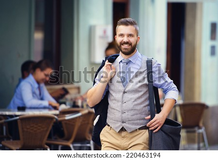 Handsome hipster modern businessman with briefcase walking in town - stock photo