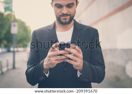 handsome hipster modern man using smart phone in the city - stock photo
