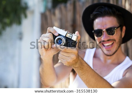 Handsome hipster photographer with a vintage film camera shooting outdoors