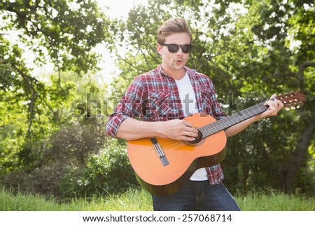 Handsome hipster playing the guitar on a sunny day
