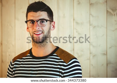 Handsome hipster posing for camera on wooden background - stock photo