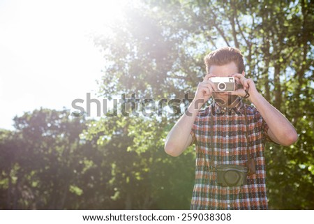 Handsome hipster using vintage camera on a summers day - stock photo