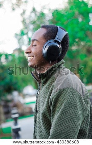 Handsome hispanic black man wearing green sweater in outdoors park area, headphones on covering ears and smiling enjoying some music, profile angle - stock photo