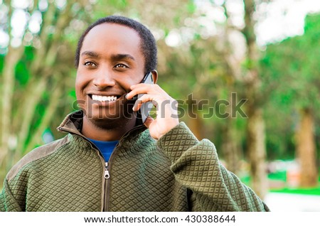 Handsome hispanic black man wearing green sweater in outdoors park area holding up phone to ear and talking happily while laughing - stock photo