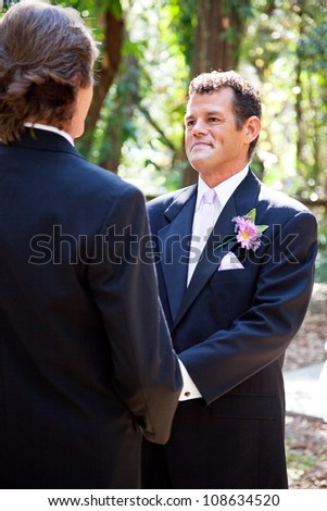 Handsome hispanic groom marrying his same sex partner in an outdoor wedding ceremony. - stock photo