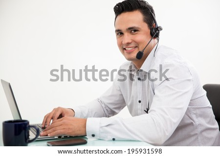 Handsome Hispanic man wearing a headset and taking a call from a customer at work - stock photo