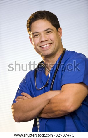 Handsome Hispanic man wearing scrubs and stethoscope. - stock photo