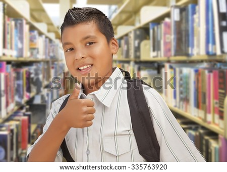 Handsome Hispanic Student Boy with Back Pack and Thumbs Up in the Library. - stock photo