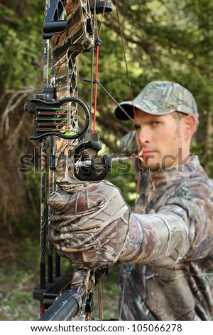 handsome hunter shooting a compound bow closeup - stock photo