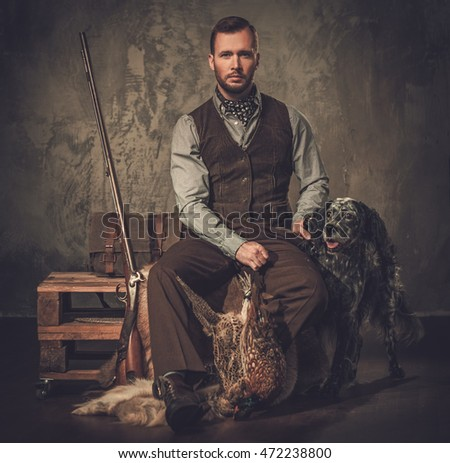 Handsome hunter with a english setter and shotgun in a traditional shooting clothing on a dark background.