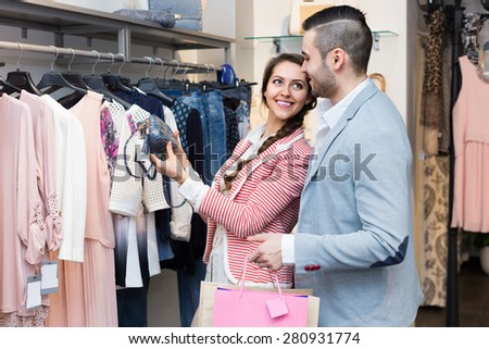 Handsome husband helping happy woman to choose new clothes - stock photo