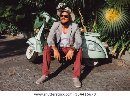 handsome in a light jacket, hat and red trousers, sunglasses with mustache and beard about posing retro scooter, fashionable clothes, brutal man, stylish outfit, Tiffany, walk down the street - stock photo