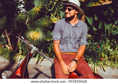 handsome in a light jacket, hat and red trousers, sunglasses with mustache and beard about posing retro scooter, fashionable clothes, brutal man, stylish outfit, Red, walk down the street - stock photo