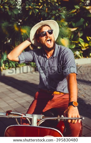 handsome in a light jacket, hat and red trousers, sunglasses with mustache and beard about posing retro scooter, fashionable clothes, brutal man, stylish outfit,, walk down the street,crazy man,happy  - stock photo