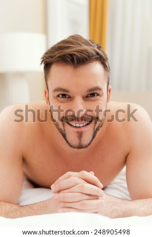 Handsome in bed. Handsome young shirtless man lying in bed and smiling - stock photo