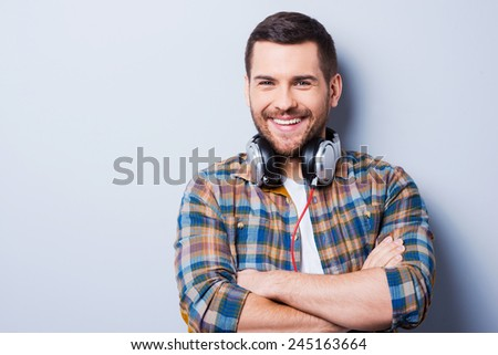 Handsome in headphones. Handsome young man wearing headphones on his neck and smiling while standing against grey background - stock photo