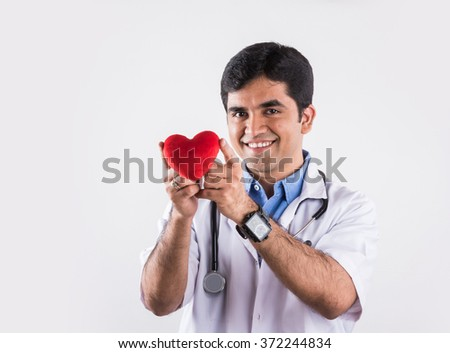 handsome indian doctor holding heart stuffed toy, doctor with red heart, asian doctor and heart care concept, isolated on white background, heart in hands of doctor - stock photo