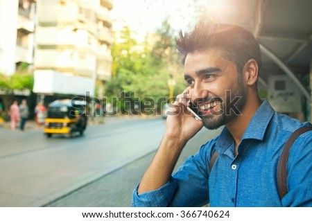 Handsome Indian guy talking on a phone  - stock photo
