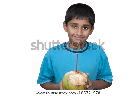 Handsome Indian kid cooling off with fresh coconut - stock photo