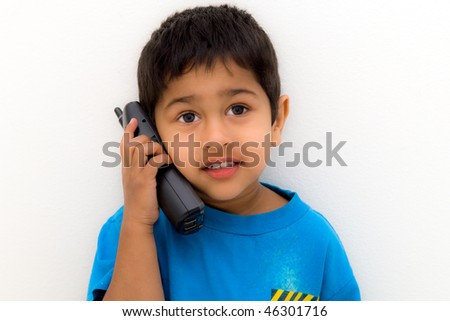 handsome indian kid speaking on the phone - stock photo