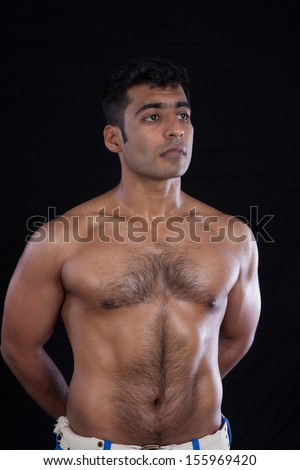 Handsome Indian man, with bare chest, showing his muscles and  body hair, looking thoughtfully at the camera   - stock photo