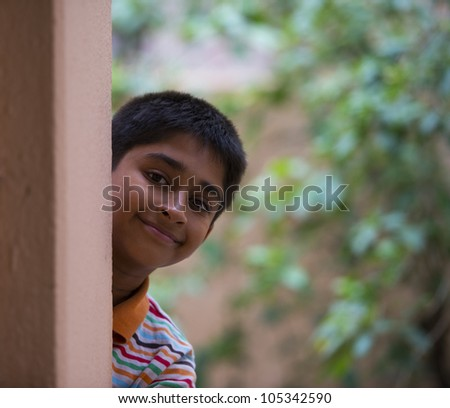 Handsome Indian toddler standing outdoor thinking - stock photo
