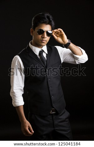 Handsome Indian young businessman posing on black background. - stock photo