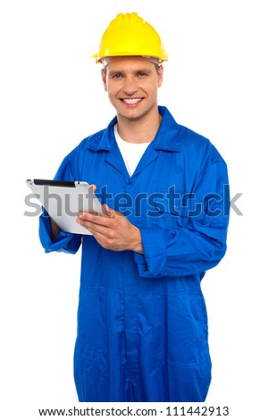 Handsome industrial contractor using wireless tablet device, looking at camera and smiling