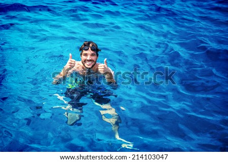 Handsome instructor of swimming wearing goggles in the pool, having fun in the water, summer adventure, travel and vacation concept