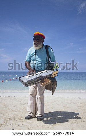 Handsome jamaican old rasta singing on the beach - stock photo