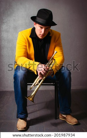 Handsome jazz trumpet player in hat and yellow jacket with trumpet. Portrait of brutal young musician holding trumpet posing in studio - stock photo