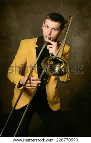 Handsome jazzer man playing the trombone. Portrait of young musician in yellow jacket with trombone posing in studio - stock photo