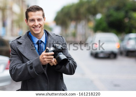 handsome journalist holding a camera in the city in the rain - stock photo