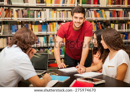 Handsome Latin man helping his colleagues out by explaining some of his work at the library - stock photo