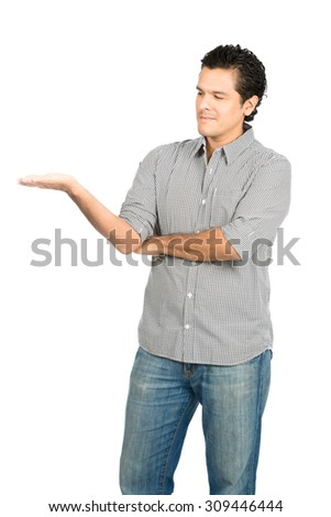 Handsome latino man wearing button down dress shirt looking down at hand out to the side displaying imaginary inserted product on flat open empty palm. Vertical - stock photo