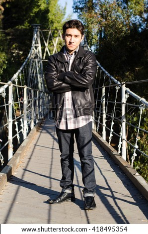 Handsome Latino teen in a leather jacket standing on a suspension bridge, arms crossed - stock photo
