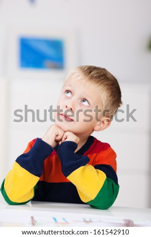 Handsome little blond boy in a colorful strip top sitting thinking with his chin on his hands and eyes raised to the ceiling - stock photo