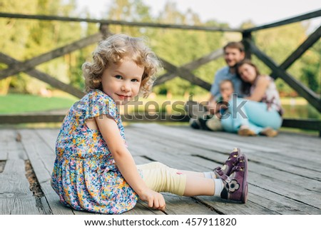 Handsome little blonde girl in dress with curly hair sitting outdoors in front of mother father and brother.