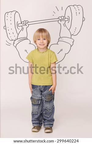 Handsome little boy dreaming about huge muscles. Boy with blond hair in yellow T-shirt and jeans lifting 100 kilos barbell. - stock photo