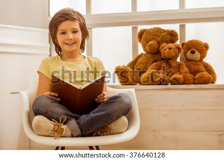 Handsome little boy holding a book, looking in camera and smiling while sitting on a chair near the window - stock photo