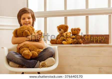 Handsome little boy hugging a teddy bear, looking in camera and smiling while sitting on a chair near the window - stock photo
