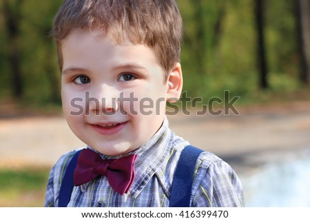 Handsome little boy in shirt and bow tie smiles in sunny green park - stock photo