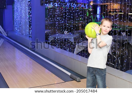 handsome little boy playing bowling