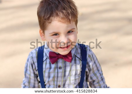 Handsome little boy with bow tie looks at camera outdoor, top view - stock photo