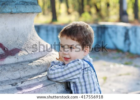 Handsome little boy with bow tie stands near old fountain in park, shallow dof - stock photo