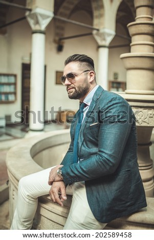 Handsome looking man in smart combination dressed in blue blazer and cream pants wearing sunglasses,sitting on the fountain, outside portrait - stock photo