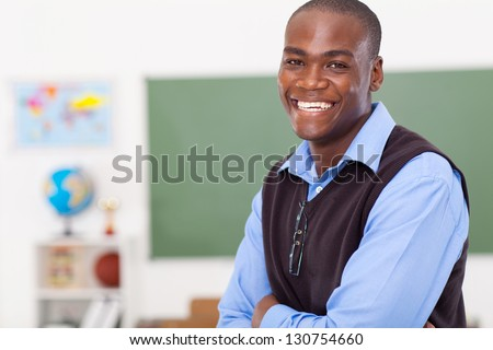 handsome male african primary school teacher in classroom - stock photo