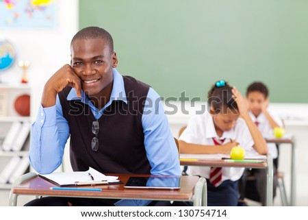 handsome male African primary school teacher in classroom