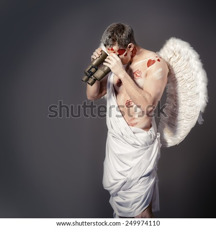 Handsome male angel Cupid looking for something with binoculars. Valentine's day. Love concept. - stock photo