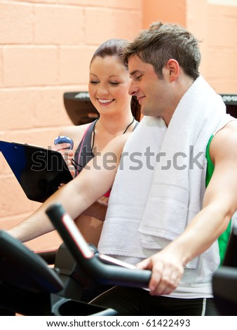 Handsome male athlete exercising on a bicycle with his personal coach in a fitness center